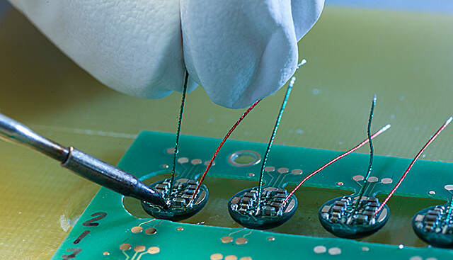 Hand soldering of wire strands (under binocular loupe) -